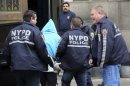 New York City police officers escort Julio Acevedo, in light blue hood, into the 78th precinct, Thursday, March 7, 2013 in New York. Acevedo was arrested in Pennsylvania on Wednesday after a friend arranged his surrender. (AP Photo/Mary Altaffer)