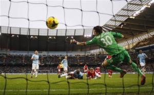 Arsenal's Per Mertesacker heads and scores a goal during their English Premier League soccer match against Manchester City at the Etihad stadium in Manchester