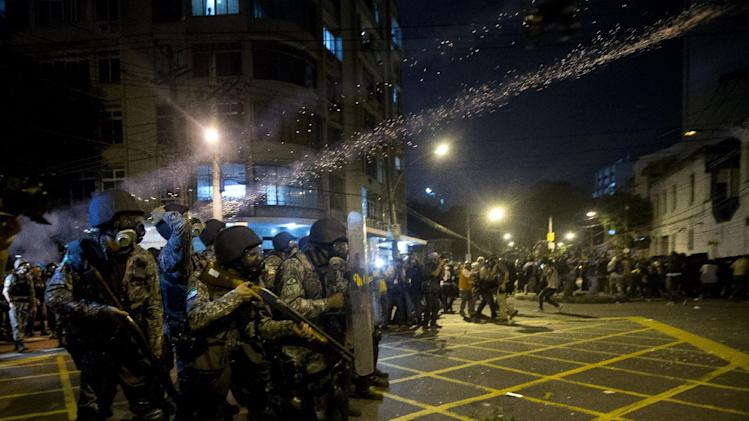 Military police fire tear gas at protestors during an anti-government protest near the Maracana stadium during the Confederations Cup final soccer match between Brazil and Spain, in Rio de Janeiro, Brazil, Sunday, June 30, 2013. Anti-government protesters are marching Sunday near the Maracana football stadium during a major international match, venting their anger about the billions of dollars the Brazilian government is spending on major sporting events rather than public services.(AP Photo/Silvia Izquierdo)
