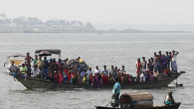 Relatives and locals watch a rescue operation after the M.V. Miraj-4 ferry capsized in the Meghna river at Rasulpur in Munshiganj district
