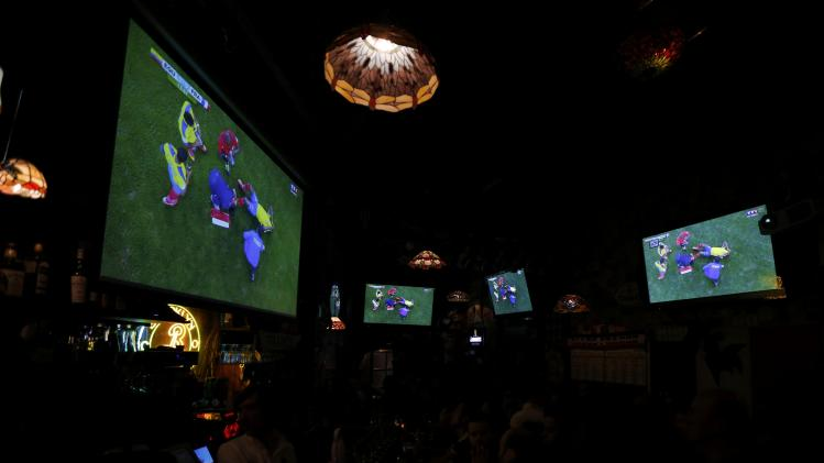 Multiple large screens hang in a bar as France team soccer fans gather to watch a live broadcast of the 2014 World Cup Group E soccer match between Ecuador and France at the Maracana stadium in Rio de Janeiro, in Nantes