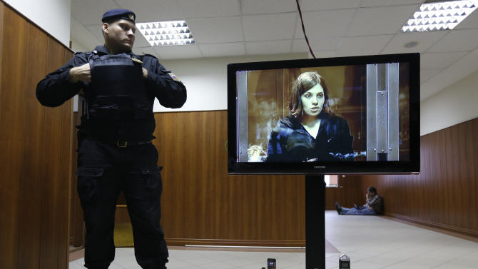A policeman watches band member Nadezhda Tolokonnikova speaking on a TV screen in a hall outside a court room of the Moscow City Court where three members of the punk band Pussy Riot are set to make their case before a Russian appeals court that they should not be imprisoned,  in Moscow, Wednesday. Oct. 10, 2012.  Their impromptu performance inside Moscow's main cathedral in February came shortly before Putin was elected to a third term. The three women were convicted in August of hooliganism motivated by religious hatred and sentenced to two years in prison. (AP Photo/Sergey Ponomarev)