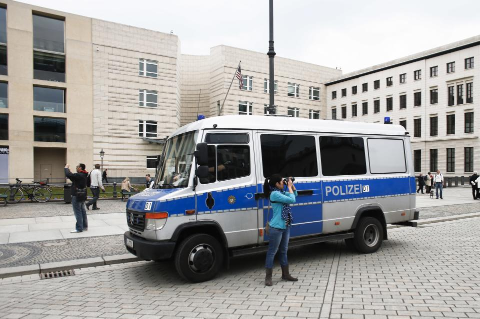 Tourists take pictures near a German police car guarding in front of the United States embassy  in Berlin, Tuesday, April 16, 2013. On Monday April 15, 2013 two bombs exploded in the crowded streets at the Boston marathon in the United States. (AP Photo/Markus Schreiber)