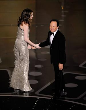 Comedian Billy Crystal is greeted by Anne Hathaway before speaking during the 83rd Academy Awards on Sunday, Feb. 27, 2011, in the Hollywood section of Los Angeles. (AP Photo/Mark J. Terrill)