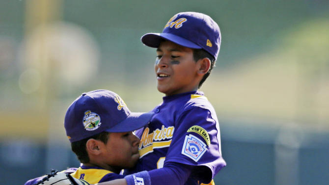 Aguadulce, Panama second baseman Edwin Nieto, right, leaps into the arms of third baseman Daniel Cruz (1) after Cruz made a diving stop and threw from his knees to get Tokyo's Satoru Aoyama at first to end the fourth inning of an International pool baseball game at the Little League World Series tournament in South Williamsport, Pa., Wednesday, Aug. 22, 2012. Tokyo won 4-1.(AP Photo/Gene J. Puskar)