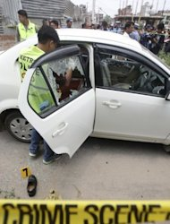 Nepalese crime officers examine the car in which a Supreme Court judge was shot in Kathmandu on Thursday. Judge Rana Bahadur Bam, a Supreme Court justice for four years, had been suspended from hearing cases after being accused of taking bribes in return for giving lenient sentences to criminals