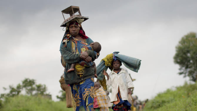 """A displaced Congolese family carry their belongings on the road between Rutshuru and Goma, after the village of Kibumba was occupied by an armed militia consisting of current or former members of the """"National Congress for the Defence of the People"""", according to those fleeing, in Congo Tuesday, May 8, 2012. Mutinous soldiers formerly from the armed militia """"National Congress for the Defence of the People"""" and linked to Congolese ex-general Bosco Ntaganda, who is wanted for alleged war crimes by the International Criminal Court, say they have formed a new rebel group called the """"March 23 Movement"""", led by a colonel who was formerly the No. 2 in the army under Ntaganda. (AP Photo/Marc Hofer)"""