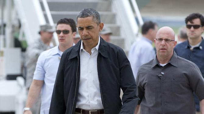President Barack Obama walks across the tarmac to greet people as he arrives on Air Force One, Sunday, May 26, 2013, at Tinker Air Force Base in Midwest City, Okla., en route to the Moore, Okla., to see the response to the severe tornadoes and weather that devastated the area. He will also visit with the families affected, and with first responders. (AP Photo/Carolyn Kaster)