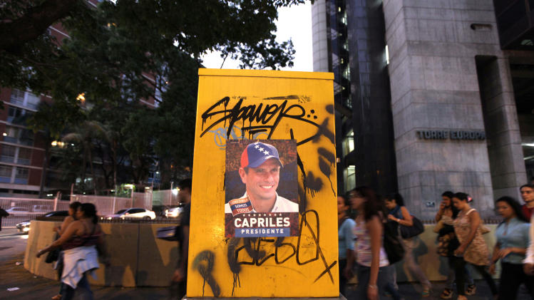 People walk behind a poster of opposition presidential candidate Henrique Capriles in Caracas, Venezuela, Friday, April 12, 2013. Capriles is running against interim President Nicolas Maduro in Sunday's presidential election. (AP Photo/Ariana Cubillos)