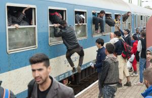 Migrants climb out of the windows of a train after …