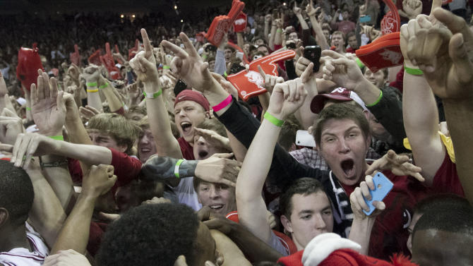 Arkansas fans storm the court as they celebrate after their 80-69 win over No. 2 Florida in an NCAA college basketball game in Fayetteville, Ark., Tuesday, Feb. 5, 2013. (AP Photo/Gareth Patterson)