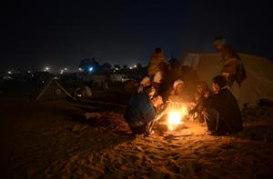 Traders gather around a fire before dawn at the camel…