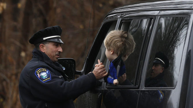 Easton police officer J. Sollazzo clasps hands with a young student returning to Hawley School, Tuesday, Dec. 18, 2012, in Newtown, Conn.  Classes resume Tuesday for Newtown schools except those at Sandy Hook. Buses ferrying students to schools were festooned with large green and white ribbons on the front grills, the colors of Sandy Hook. At Newtown High School, students in sweatshirts and jackets, many wearing headphones, betrayed mixed emotions.  Adam Lanza walked into Sandy Hook Elementary School in Newtown,  Friday and opened fire, killing 26 people, including 20 children, before killing himself.(AP Photo/Jason DeCrow)