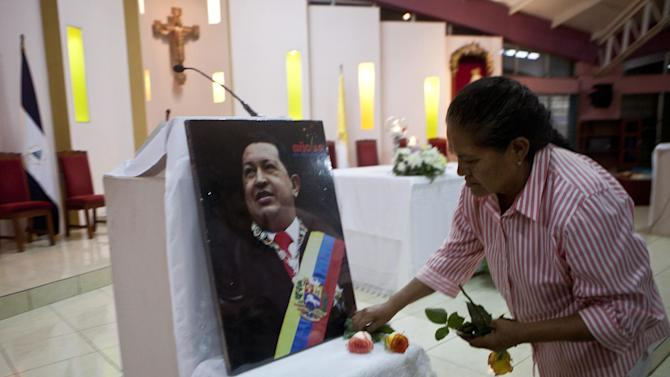 "A woman places flowers in front of an image of Venezuela's President Hugo Chavez in preparation for a mass in support of him in Managua, Nicaragua, Wednesday Dec. 12, 2012. Venezuela's Information Minister Ernesto Villegas expressed hope about the Chavez's returning home for his Jan. 10 swearing-in for a new six-year term after his cancer surgery in Cuba, but said in a written message on a government website that if Chavez doesn't make it, ""our people should be prepared to understand it."" (AP Photo/Esteban Felix)"