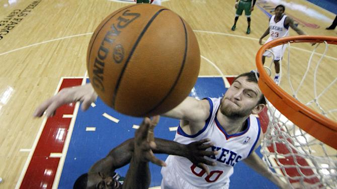 Boston Celtics' Brandon Bass, left, tries to get a shot past Philadelphia 76ers' Spencer Hawes during the first half of Game 3 of an NBA basketball Eastern Conference semifinal playoff series, Wednesday, May 16, 2012, in Philadelphia. (AP Photo/Matt Slocum)