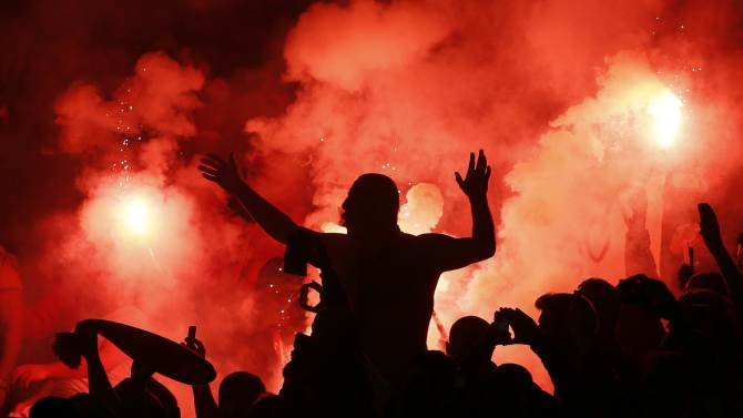 Galatasaray fans light flares during their Champions League soccer match against Arsenal at the Emirates Stadium in London
