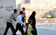 Syrian rebel stands on a street corner while a family flees the area as on going clashes with government troops take place in the Salhin district of the northern city of Aleppo