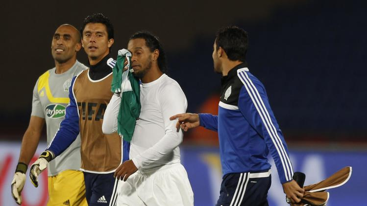 Atletico Mineiro's Ronaldinho reacts near Raja Casablanca players after their FIFA Club World Cup semi-final match at Marrakech stadium