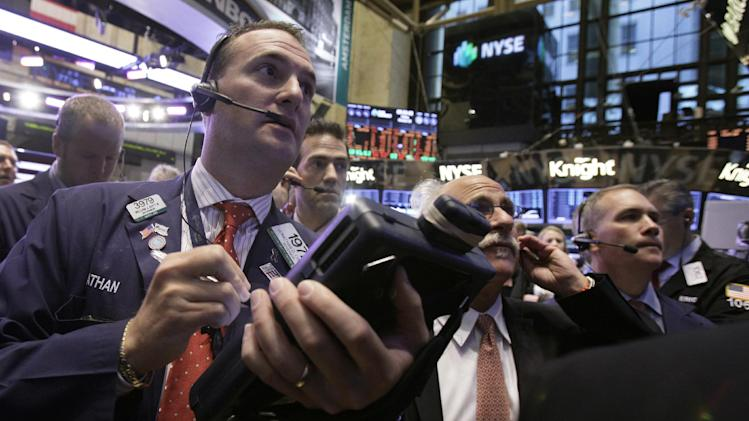 Jonathan Corpina, left, works with fellow traders on the floor of the New York Stock Exchange Friday, Oct. 5, 2012. Stocks are rising in early trading on Wall Street after the government reported that the U.S. unemployment rate fell below 8 percent for the first time in almost four years. (AP Photo/Richard Drew)