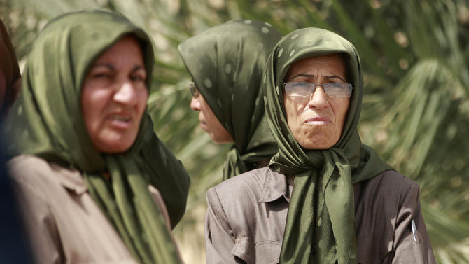 FILE - In this Tuesday, Sept. 11, 2012, file photo, members of the Mujahedeen-e-Khalq organization are seen inside Camp Liberty in Baghdad, Iraq. The Iranian exile group living in the camp near Baghdad airport said Saturday, June 15, 2013, it came under attack from rockets that caused casualties among its members, according to camp spokesman Shahriar Kia. (AP Photo/ Hadi Mizban, File)
