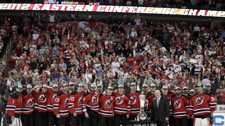Members of the New Jersey Devils stand near the Eastern Conference trophy after beating the New York Rangers 3-2 in overtime of Game 6 of the NHL hockey Stanley Cup Eastern Conference finals, Friday, May 25, 2012, in Newark, N.J. (AP Photo/Julio Cortez)