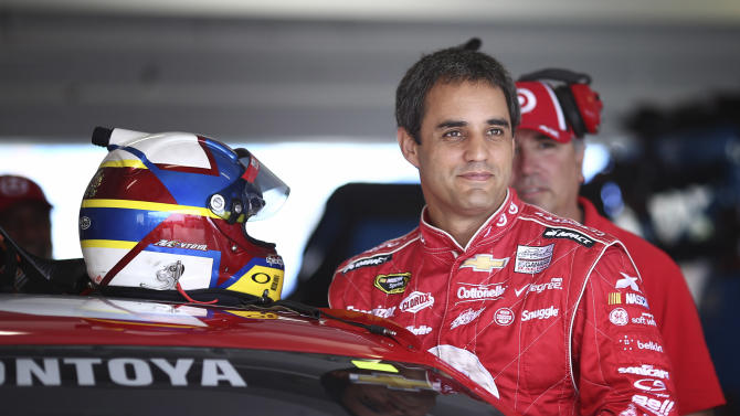 FILE - In this Nov. 15, 2013 file photo, Juan Pablo Montoya, of Colombia, climbs into his car for NASCAR practice at Homestead-Miami Speedway in Homestead, Fla. Montoya is turning laps in an Indy car again during his first official test with Penske Racing. The Penske test at Sebring International Raceway on Monday, Nov. 25, 2013, is Montoya's first time driving an Indy car since 2000. (AP Photo/J Pat Carter, File)