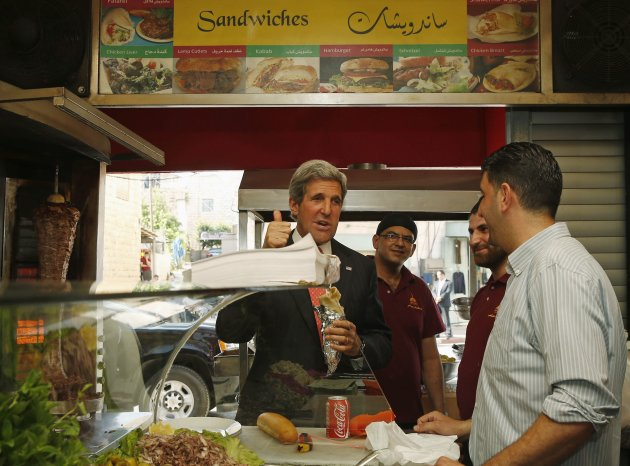 U.S. Secretary of State John Kerry displays his approval of the food as he  visits a restaurant in the West Bank city of Ramallah