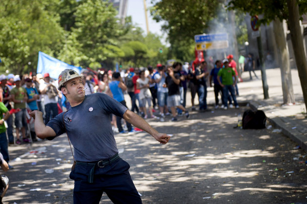 A miner throws a firecracker at the Industry Ministry during a demonstration to protest against cuts in Madrid, Thursday, May 31, 2012. Miners coming from all around Spain demonstrate in Madrid amid fear on losing their jobs. Spain is moving closer to the financial tipping-point that could force it to ask for a bailout as the country's borrowing costs neared unsustainable levels Wednesday. The country's economic fortunes have gone from boom to bust over the past decade.(AP Photo/Daniel Ochoa de Olza)