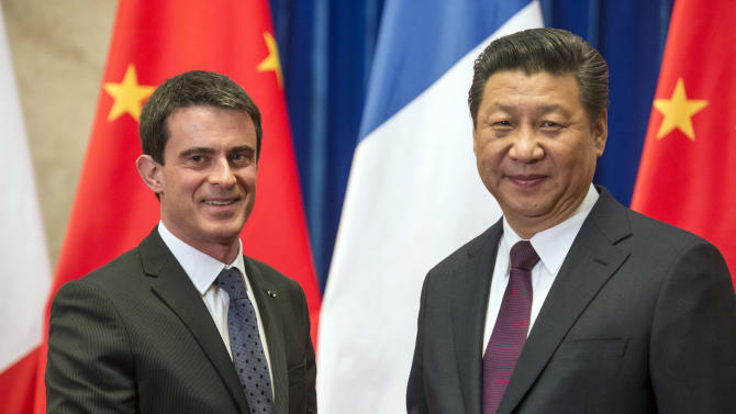 French Prime Minister Manuel Valls shakes hands with Chinese President Xi Jinping at the Great Hall of the People in Beijing