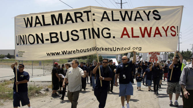FILE - In this Thursday, May 14, 2009 file photo, about 100 demonstrators march down a highway as union organizers, clergy, students and others demonstrate at a Wal-Mart distribution center in Fontana, Calif. For years, the world's largest retailer has tried to repair a reputation that's been damaged by decades of criticism and legal troubles. In April 2012, allegations that Wal-Mart paid bribes to officials in Mexico threaten to derail Wal-Mart's attempts to improve its image. (AP Photo/Reed Saxon)