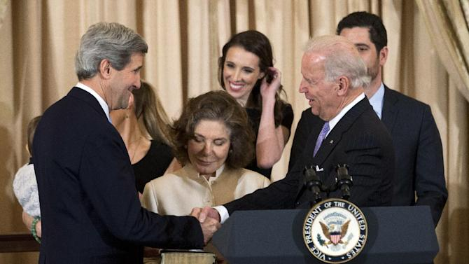 FILE - In this Feb. 6, 2013, file photo, U.S. Secretary of State John Kerry, left, with his wife Teresa Heinz Kerry, center, is congratulated by Vice President Joe Biden, right, during the ceremonial swearing-in as the 68th secretary of state at the State Department in Washington,. Witnessing the ceremony are Kerry's daughters Vanessa Kerry, obscured, and Alexandra Kerry, back center, and stepson Christopher Heinz, back right. Kerry has spent nearly half of his first year as secretary of state jumping on and off airplanes and diving headlong into some of the world's most difficult problems. (AP Photo/Manuel Balce Ceneta)