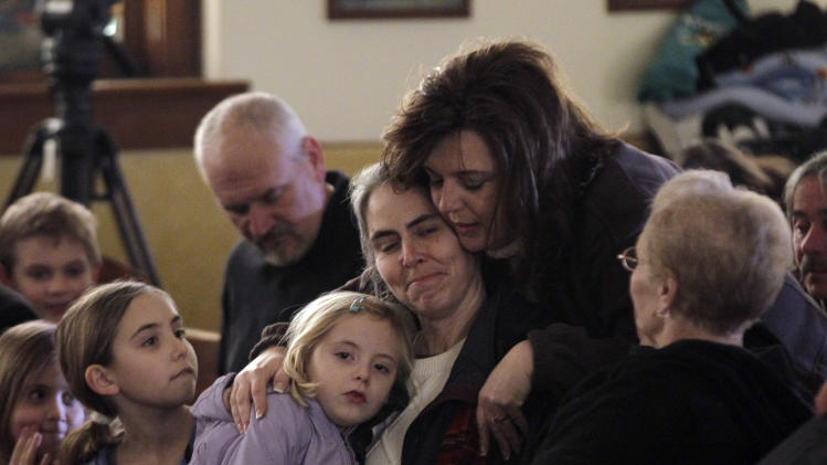 Residents attending mass at St. Francis Xavier Catholic Church hugs before the start of services in Henryville, Ind., Sunday, March 4, 2012. The church was in the path of a tornado that destroyed much of the town. Three people were killed in Southern Indiana by Tornados on Friday.  (AP Photo/Michael Conroy)