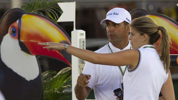 """Granddaughter and sole heiress of the late shipping tycoon Aristotle Onassis, Athina Onassis, right, and her husband, Brazilian professional show jumper Alvaro """"Doda"""" de Miranda, check the track at the Athina Onassis International Horse Show 2012 in Rio de Janeiro, Brazil, Thursday, Oct. 4, 2012. The show which is considered the largest equestrian event in Latin America brings together the best riders in the world competing in jumping and dressage. (AP Photo/Silvia Izquierdo)"""