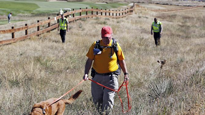 Denis McLaughlin leads his search and rescue dog through a field of tall grass searching for ten-year-old Jessica Ridgeway near her home in Westminster, Colo., on Monday, Oct. 8, 2012. The youngster has been missing since she left her home Friday morning on her way to school. (AP Photo/Ed Andrieski)