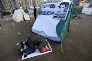 An Egyptian protester prays next to a tent with a poster of a man killed by the security forces during the revolution with Arabic writing that reads &quot; Shihab Al-Din Ahmed, the martyr of freedom&quot;, in Tahrir Square, in Cairo, Egypt, Thursday, Jan. 26, 2012. Egyptian protesters camp in Tahrir Square as they mark the first anniversary of the popular uprising that unseated President Hosni Mubarak. (AP Photo/Khalil Hamra)