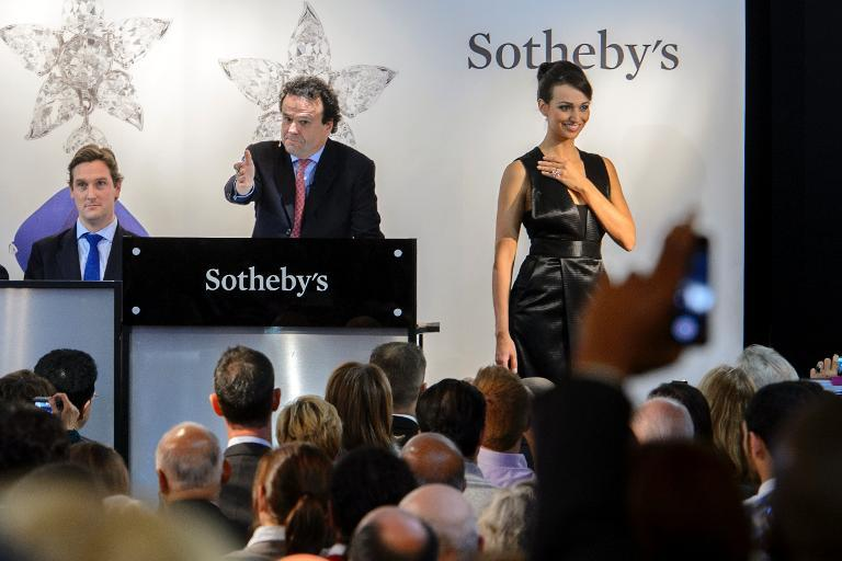 """Chairman of auctioneers Sotheby's jewellery division in Europe and the Middle East, David Bennett (C) conducts the auction of the """"Pink Star"""" diamond on November 13, 2012 in Geneva"""