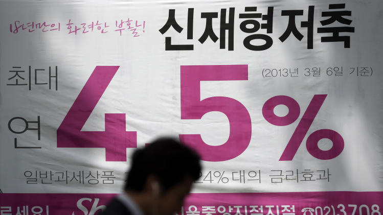 A man walks by an advertisement board showing bank's interest rate, in Seoul, South Korea, Thursday, May 9, 2013. South Korea's central bank on Thursday cut its benchmark interest rate for first time in seven months, a surprise move apparently meant to counter the weakness of the yen. (AP Photo/Lee Jin-man)