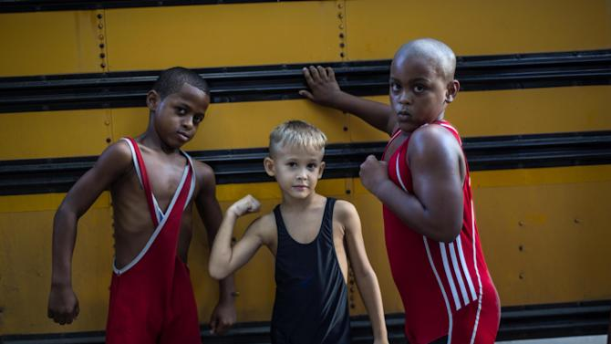 """In this Oct. 16, 2014 photo, young wrestlers Braimond Sanchez, from left, Raimel Lazaro and Junior Lazaro strike a pose for a photo, during a training session in a park in Old Havana, Cuba. About 20 children are learning to wrestle under the watchful eye of former wrestler Michael Guerra. When asked why they chose wrestling in baseball-loving Cuba, they shout in unison: """"To be like Mijain Lopez!"""" Lopez has won two Olympic gold medals in Greco-Roman wrestling, as well as five world championships, and is one of Cuba's most heralded and popular athletes. (AP Photo/Ramon Espinosa)"""