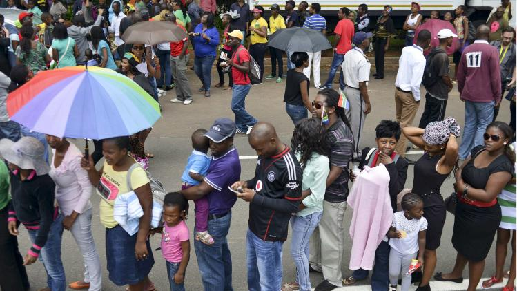 People wait for transport to take them to view the body of former South African President Nelson Mandela, at Union Buildings in Pretoria