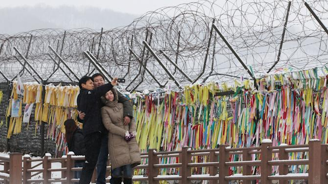 Visitors take pictures in front of the barbed wire fence decorated with messages wishing for the reunification of the two Koreas at Imjingak in Paju near the border village of the Panmunjom,  South Korea, Tuesday, Jan 1, 2013.  North Korean leader Kim Jong Un called on his country in a New Year's Day speech Tuesday to focus on economic improvements with the same urgency scientists put into the launch of a long-range rocket last month.(AP Photo/Ahn Young-joon)