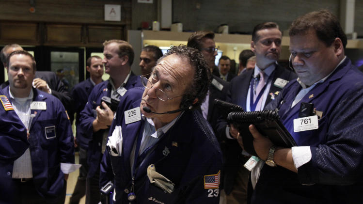 FILE - In this Friday, Aug. 3, 2012 file photo, trader Steven Kaplan, center, checks prices as he waits for shares of AIG to resume trading on the floor of the New York Stock Exchange. The rating agency Standard & Poor's stunned the world a year ago by stripping the U.S. government of its prized AAA bond rating. A year later, S&P's historic move looks like a non-event. Long-term interest rates are sharply lower, the Dow Jones industrial average has reversed course and is now up more than 1,600 points. The dollar has rallied, and gold prices are down from where they were when S&P lowered the boom  (AP Photo/Richard Drew, File)