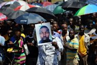 A South African miner on October 6 holds the portrait of a colleague who died during clashes with police. Representatives of 12,000 fired Anglo American Platinum workers in South Africa said Sunday they plan to lay murder charges against police after their colleague was killed in clashes with the authorities