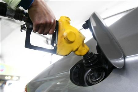 An attendant tops up petrol for a vehicle at a gas station in Taipei