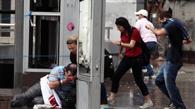 A man falls injured as Turkish riot police spray water cannon at demonstrators who remained defiant after authorities evicted activists from an Istanbul park, making clear they are taking a hardline against attempts to rekindle protests that have shaken the country, in city's main Kizilay Square in Ankara, Turkey, Sunday, June 16, 2013.(AP Photo/Burhan Ozbilici)