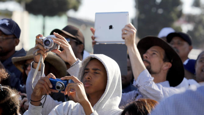 Spectators photograph the space shuttle Endeavour as it slowly moves down Martin Luther King Blvd. in Los Angeles Sunday, Oct. 14, 2012. In thousands of Earth orbits, the space shuttle Endeavour traveled 123 million miles. But the last few miles of its final journey are proving hard to get through. Endeavour's 12-mile crawl across Los Angeles to the California Science Museum hit repeated delays Saturday, leaving expectant crowds along city streets and at the destination slowly dwindling. Officials estimated the shuttle, originally expected to finish the trip early Saturday evening, would not arrive until later Sunday. (AP Photo/Alex Gallardo)