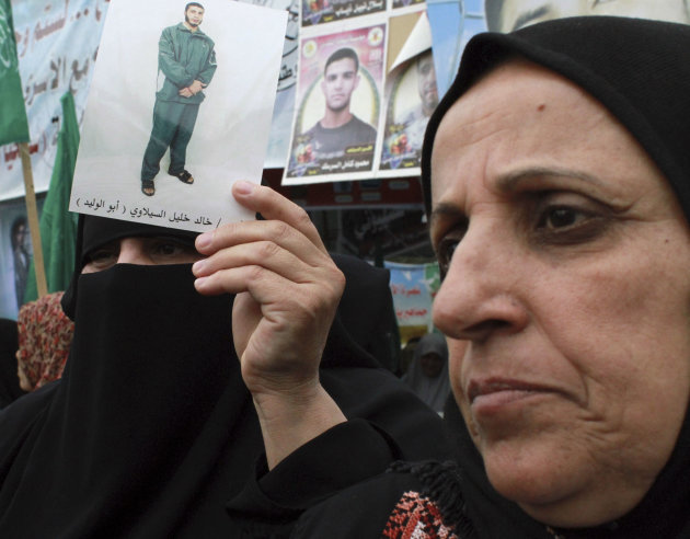 Palestinian women, one holding a photograph of a prisoner, participate in a solidarity protest with Palestinian prisoners jailed in Israeli, in Gaza City, Monday, May 14, 2012. Hundreds of Palestinian