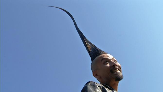 In this image taken from video, Kazuhiro Watanabe, 40, a fashion designer from Tokyo, shows off his 3-foot-8-point-6-inch hairdo in New York City's Washington Square Park on Wednesday, Sept. 12, 2012. To make it stand upright he says it takes stylists two hours, one can of gel and three cans of hairspray. The New York appearance was to promote the newest version of the Guinness World Records book, which for the first time includes Watanabe. (AP Photo/Ted Shaffrey)