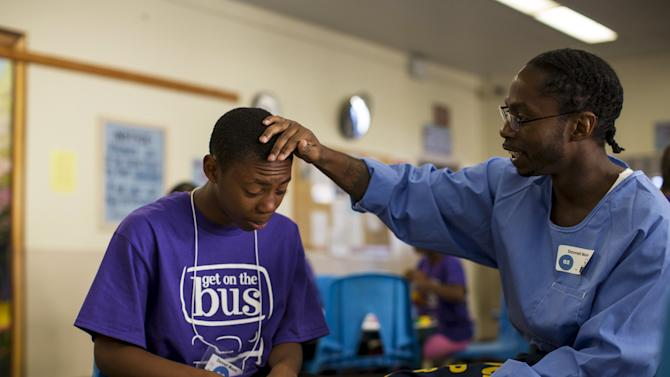 "Inmate Donnell Moore touches the head of his son Donnell Moore during a special Father's Day visit part of the ""Get On The Bus"" program at California Men's Colony in San Luis Obispo"