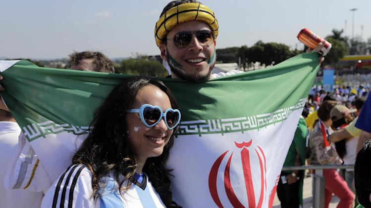 Fans of Iran ( holding an Iranian national flag ) and Argentina, pose for the cameras as they arrive to attend the group F World Cup soccer match between Argentina and Iran at the Mineirao Stadium in Belo Horizonte, Brazil, Saturday, June 21, 2014