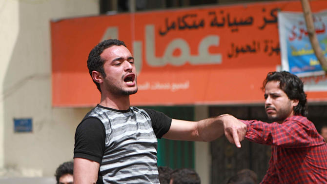 """This April 1, 2011 photo shows activist Ahmed Douma chanting slogans during a march to Tahrir Square demanding prosecution of members of former President Hosni Mubarak's regime in Cairo, Egypt. An Egyptian prosecutor says prominent Douma was arrested and referred to a speedy trial for insulting the country's president in comments he made on TV, in the first such case. Prosecutor Mohammed Tanikhi said Thursday, May 2, 2013 that Douma's trial begins Sunday. He was arrested Tuesday after a Muslim Brotherhood member complained that Douma called Morsi a """"killer"""" and a """"criminal"""", blaming him for a violent security crackdown on protesters in the coastal city of Port Said that left 40 people killed. (AP Photo/Sarah Carr)"""